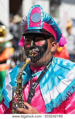 June 17 2017 Pujili Ecuador: marching band member dressed in colourful costume opening the Corpus Christi parade
