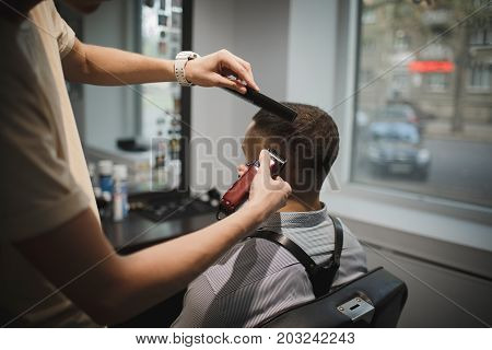 Back view of hairdresser's hands shaving male client's head. A shaving process on a blurred background. Hairstylist serving a brunette client at barbershop. Beauty, style, retro, hipster concept.
