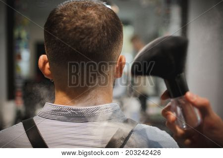 A back view of a male head next to a big black brush in a white talcum powder on a blurred background. A vintage shaving accessory for barbershops. Tools for cutting. Beauty, style, fashion concept.