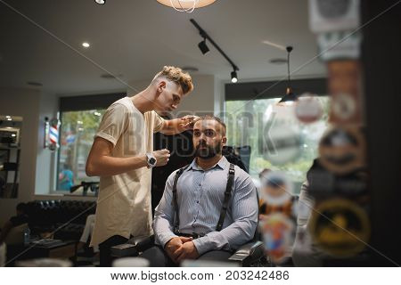 A cutting process on a blurred background. Hairstylist serving a brunette client with a beard at barbershop. Hairdresser's hands cutting male client's hair. Beauty, style, hipster concept.