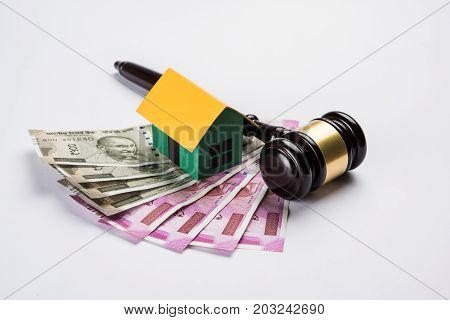 stock photo of india and real estate law, Indian law for real estate / construction company  / architects / builders or buyers showing small house model, gavel / hammer, indian currency notes