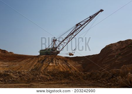 Yellow mobile crane working in the sandy quarry. An industrial moving machine in the foundation pit. Industry equipment on a blue sky background. Technology, cargo, commerce, transport concept.
