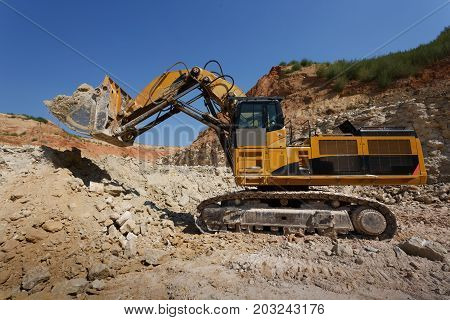 Close-up picturte of a huge excavator loading the ground on a blue sky and sandy quarry background. Excavator at sandpit during earthmoving works. Technology, cargo, commerce, transport concept.