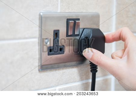 Close Up Of Hand Putting Plug Into Electricity Socket