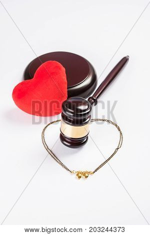stock photo of concept of breakup or divorce in India showing Gavel, stuffed red heart, mangalsutra or necklace which is a typical Hindu traditional ornament to  wear by married women in india