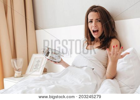 Unhappy young girl gesturing with hands and screaming while laying in bed in the morning and holding alarm clock