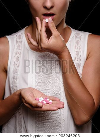 Close-up of a female hand holding colorful tablets. A tanned girl swallows pills. A young woman in a white blouse on a black background. A heap of pills in a hand. Medicine, healthcare concept.