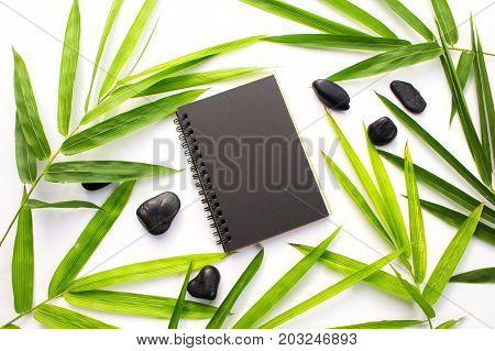 Bamboo leaf zen background. Black paper notebook mockup. Green bamboo leaf and beach pebbles flat lay. Blank page notepad top view. Spa or beauty banner template with text place. Asian style mock-up