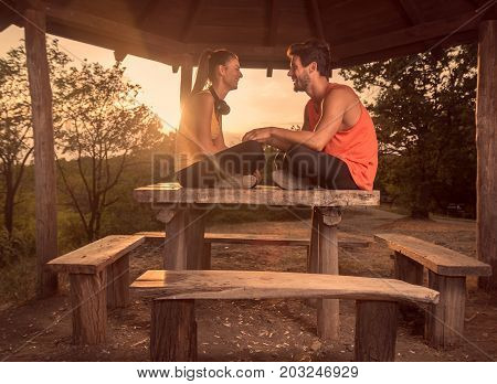 Two People, Young Couple, Smiling, Sitting On Wood Table, Outdoors, Warm Sunny Day Sun, Relaxing, Sp