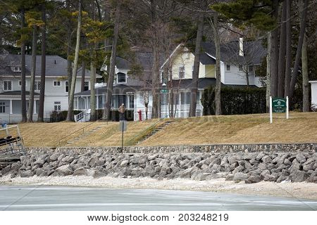 WEQUETONSING, MICHIGAN / UNITED STATES -  MARCH 30, 2017: A pedestrian walks past beachfront homes on Beach Drive in Wequetonsing.
