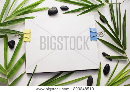 Bamboo leaf background. White sketchbook spread notebook mockup. Green bamboo leaf and sea beach pebbles flat lay. Blank page notepad top view. Natural spa or beauty banner template with text place