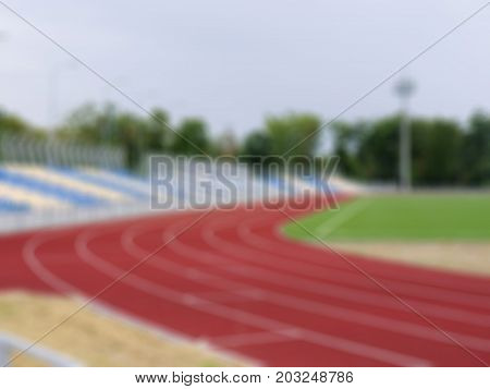 A blurred red track for running trainings and competitions as a background. Running track, stadium seats and soffits in the sports stadium. Sports, outdoors, summer concept. Copy space.
