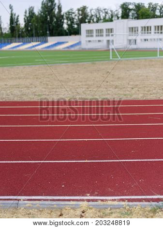 Close-up picture of a running track in the sports stadium. A bright red track for running trainings and competitions on a stadium background. Sports, outdoors, summer concept. Copy space.