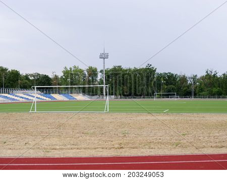 A green summer football field on a natural background. A modern football field with white gates without a grid, soffits, and plastic colorful blue and yellow seats. Sports, outdoors, football concept.