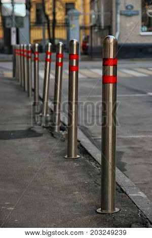 stainless steel parking bollards with red stripes along roadway on street
