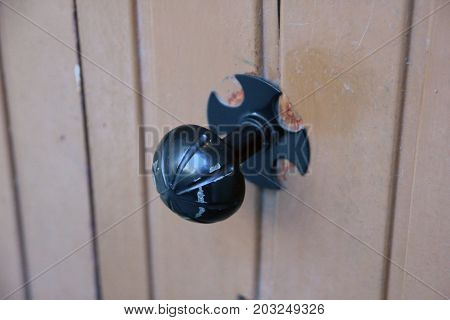 unusual black metal round door handle in shape of bowl with notches closeup