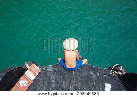 man wearing traditional vietnamese hat sitting in front of ship cruising among beautiful limestone rocks and secluded beaches in Ha Long bay, UNESCO world heritage site, Vietnam
