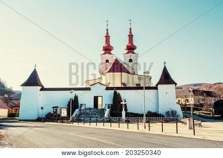 Roman catholic church in Divin village Slovak republic. Religious architecture. Retro photo filter. Jesus Christ on the cross.