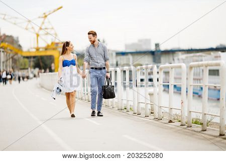 Happy couple walking outdoors on the riverside