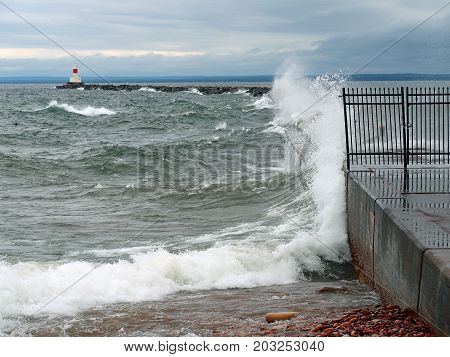 Waves of Lake Superior splash against the Presque Isle breakwater which protects the harbor at Marquette Michigan.