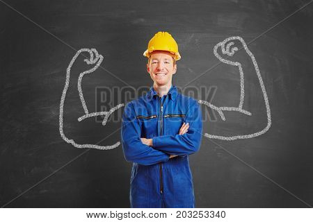 Powerful man as construction worker with chalk muscles on blackboard
