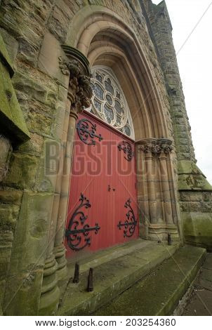 red church door with ornate arched top