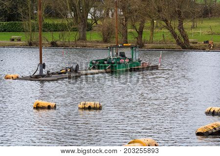 HEILIGENHAUS NRW DEUTSCHLAND - MÄRZ 03 2017: Special ship working platform in use on a small pond. Wet dredging at the Abtskuecher Teich in Heiligenhaus.