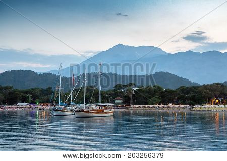 Yachts near the shore of the resort city in the evening against the backdrop of the silhouette of the mountains