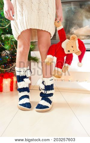 Teenage girl in cozy warm striped woolen blue socks with pompons holding christmas teddy bear toy. Indoors.