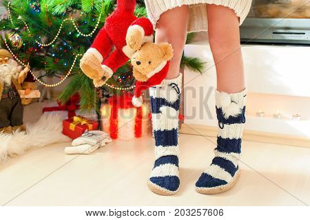 Teenage girl in cozy warm striped woolen blue socks with pompons holding teddy bear toy near illuminated christmas tree. Indoors horizontal image.