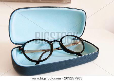 Stylish modern fashionable elegant black eyeglasses in blue leather box. Indoors horizontal close-up colorful image.