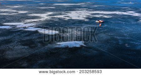A single life buoy sitting on a frozen lake