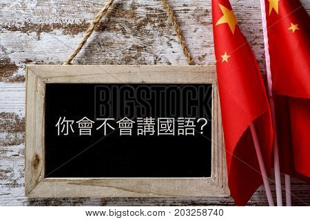 a wooden-framed chalkboard with the question do you speak Chinese? written in Chinese, and some flags of China against a rustic wooden background