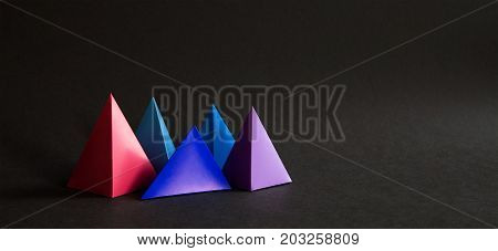 Abstract colorful geometrical composition. Three-dimensional prism pyramid objects on black paper background. Pink blue violet colored solid figures, soft focus photo. Copy space.