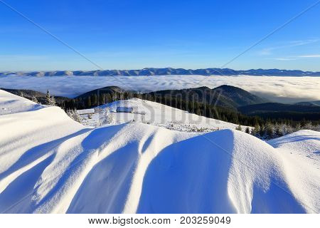 From the hills covered with snow on which fall shades opens a view on the mountain valley where small huts are located behind which stretched out spruce forest sprinkled with snow on which the sea of fog rolls over and on the horizon is towering mountain