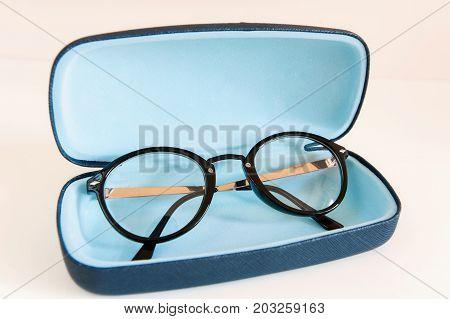 Stylish modern fashionable elegant black eyeglasses in blue leather case. Indoors horizontal close-up colorful image.