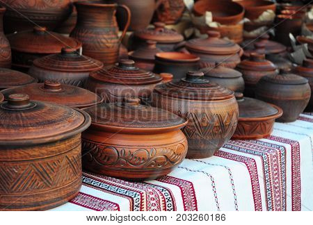 Traditional Ceramic Jugs on Decorative Towel. Showcase of Handmade Ceramic Pottery in a Roadside Market with Ceramic Pots and Clay Plates