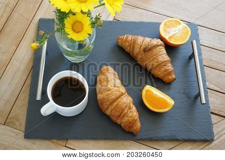 Breakfast on a tray: coffee and croissants with flowers on the wooden background, high angle view