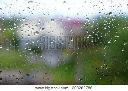 Dull landscape with many raindrops through house window on rainy autumn day