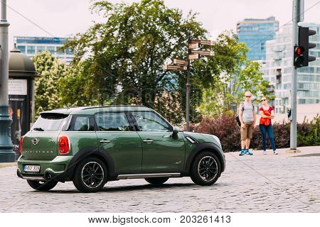 Vilnius, Lithuania - July 6, 2016: Green Color Car Mini Cooper Mini Countryman Is Moving On Street In Old Part European Town. Mini Countryman Is A Subcompact Crossover.
