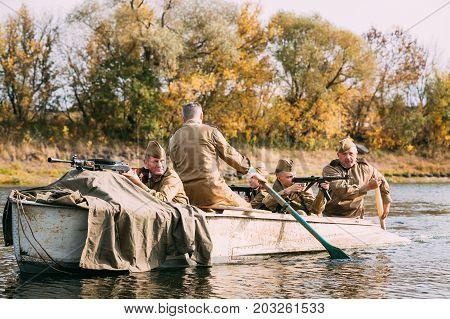 Dyatlovichi, Belarus - October 1, 2016: Group Of Men Reenactors Dressed As Russian Soviet Red Army Infantry Soldiers Of World War II Make Crossing Of River On A Boat