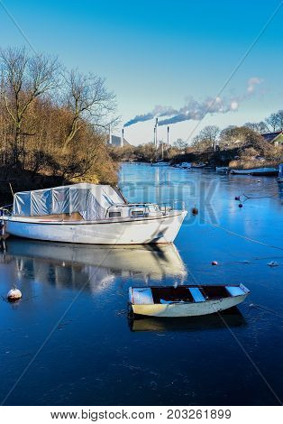 Two small boats locked on an icy river in the winter
