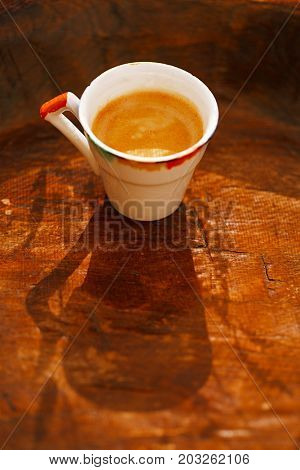 espresso coffee shot in retro cup on vintage wooden table