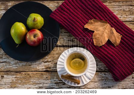 High angle view of lemon tea by fruits in plate on wooden table
