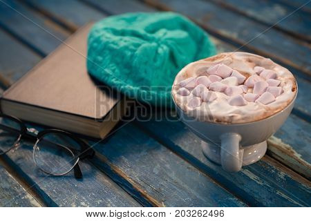 Close up of hot chocolate by cap and book on wooden table