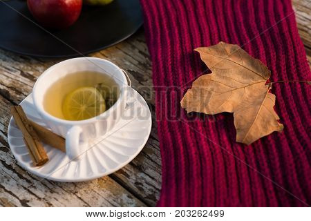 High angle view of green tea by sweater on wooden table