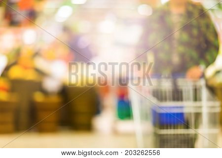 Abstract Blurred Background - Man Pushing Shopping Cart In The Supermarket