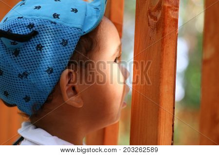 young boy looking through a fence. Sunny day