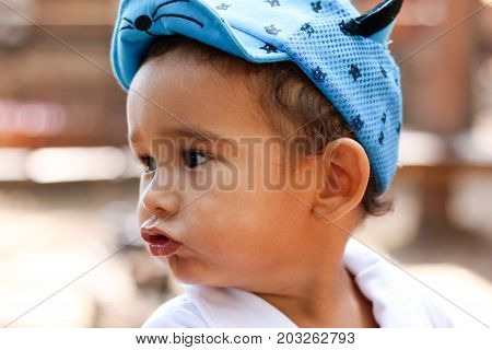 Little boy portrait in the park. chubby cheeks,