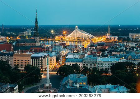 Riga, Latvia - July 2, 2016: Aerial View Of Cityscape In Evening Night Lights Illumination. Summer Top View Of St. Peter's Church, Freedom Monument And Latvian National Library. Blue Hour